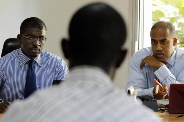AFIG chief executive Ndiaye and chief operating officer Backer listen to an employee in Senegal's capital Dakar